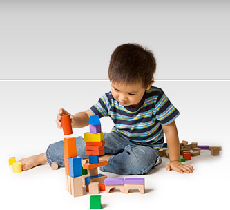 Preschool boy playing with wooden blocks.